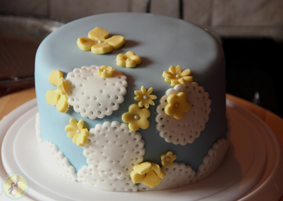 Flowers and lace cake - Blue fondant covered cake with easy white lace doilies and yellow fondant flowers