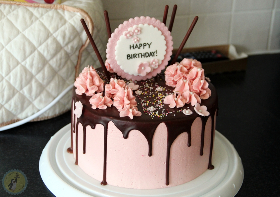 Pink Drip Cake - Covered in pink Italian meringue buttercream, decorated with a chocolate drip, buttercream swirls, sprinkles and flowers